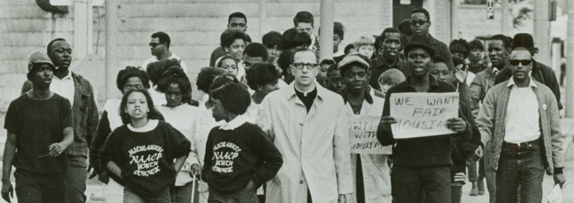 A group of predominantly young, African-American protesters with a white priest in the center of the group.