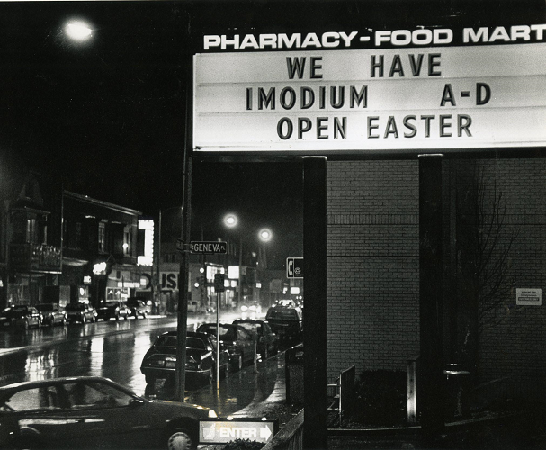 A dark rainy night on a street with lots of cars. On the right, a pharmacy sign with movable text.