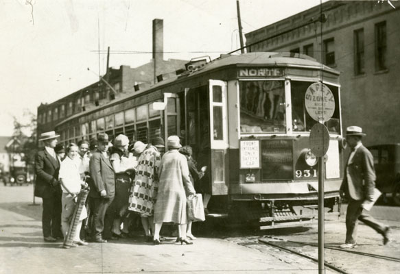 A streetcar with several people lined up to board.