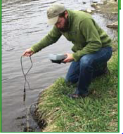 A man crouches on the bank of a body of water, and uses a suspended instrument to test the water.